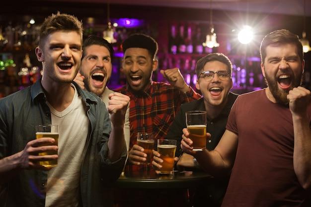 Cuatro hombres felices sosteniendo jarras de cerveza y gesticulando