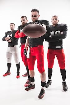 Los cuatro hombres de fitness caucásicos como jugadores de fútbol americano posando de cuerpo entero con una pelota sobre fondo blanco.