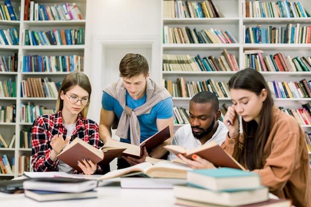 Cuatro inteligentes amigos multiétnicos concentrados sentados a la mesa en la biblioteca de la universidad y leyendo libros juntos, preparándose para el examen o la clase, haciendo la tarea en casa
