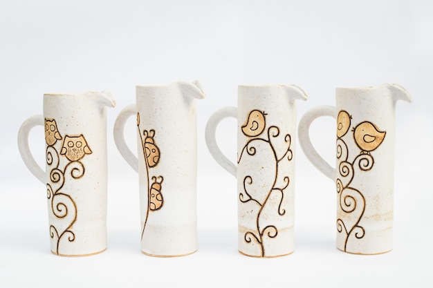 Cuatro jarras de gres cerámico con fondo blanco.