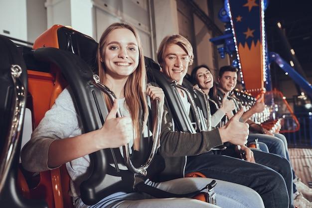 Cuatro jóvenes amigos levantan el dedo.