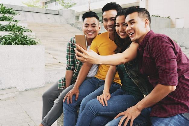 Cuatro jóvenes asiáticos vestidos casualmente sentados juntos en la calle y tomando selfie