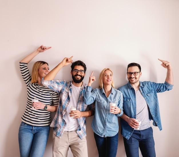 Cuatro jóvenes empresarios caucásicos sosteniendo café para ir y apuntando hacia arriba mientras se apoya en la pared blanca.