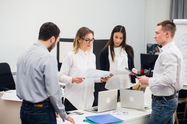 Cuatro jóvenes empresarios que trabajan en equipo se reunieron alrededor de una computadora portátil en una oficina moderna de plan abierto