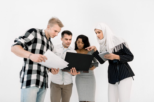 Cuatro jóvenes estudiando, mujeres y hombres hermosos multiétnicos trabajando juntos y usando una computadora portátil