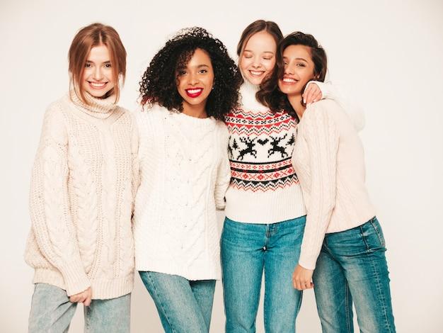 Cuatro jóvenes hermosas chicas hipster sonrientes en suéteres de invierno de moda. modelos positivos divirtiéndose y abrazándose.