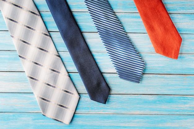 Cuatro lazos de colores en fila sobre fondo azul de madera