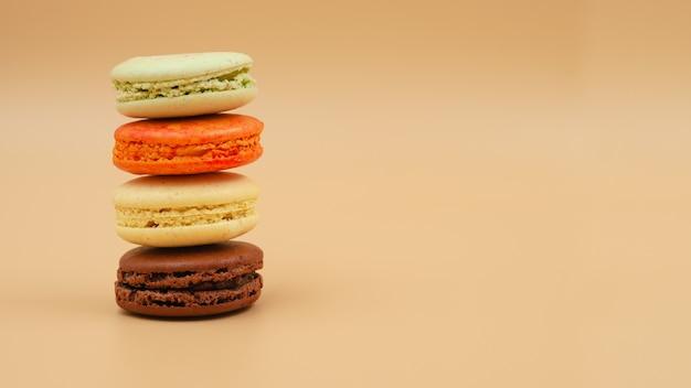 Cuatro macarons franceses apilados de colores brillantes sobre fondo melocotón espacio libre