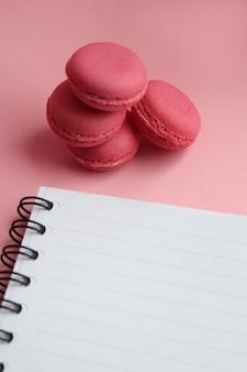 Cuatro macarrones de coral vivos, cuaderno vacío sobre un fondo rosa claro