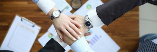 Cuatro manos juntas una sobre una vista superior. sobre la mesa hay un documento con diagrama y lupa.