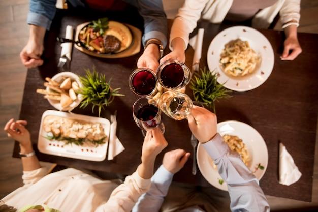 Cuatro manos con vino tinto tostado sobre mesa servida con comida