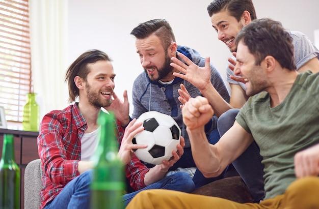 Cuatro mejores amigos hablando de partido de fútbol.