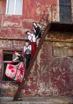 Cuatro mimos de pie en las escaleras en una pared roja.