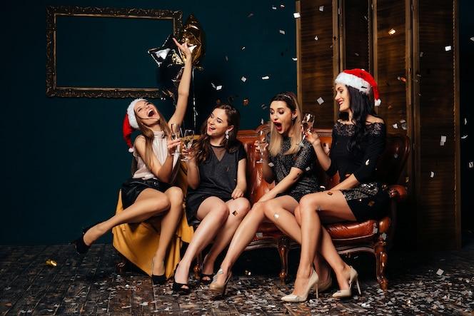 Cuatro mujeres glamour bebiendo champaña y divirtiéndose. fiesta y concepto de navidad.