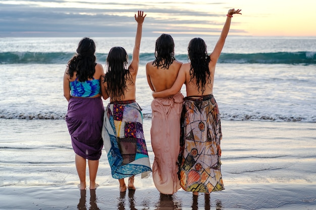 Cuatro mujeres latinas disfrutando juntos de la puesta de sol en la playa