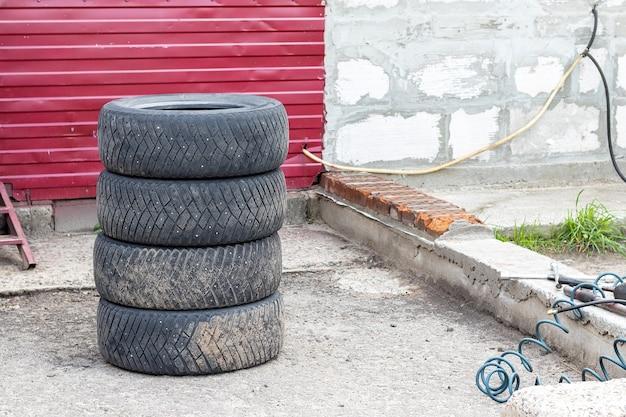Cuatro neumáticos de automóviles usados apilados uno encima del otro cerca de la tienda de neumáticos. reemplazo de la rueda en el centro de servicio de neumáticos