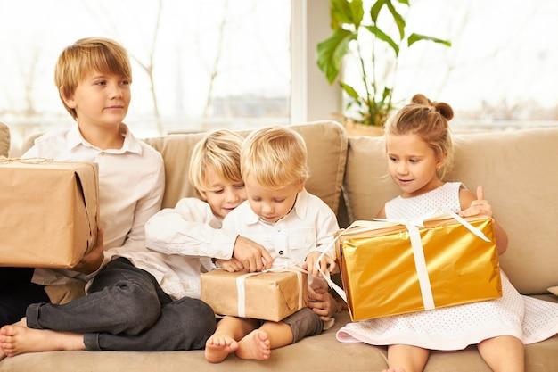 Cuatro niños caucásicos con camisas blancas idénticas y sin calcetines sentados en el sofá de la sala de estar, impacientes por abrir cajas con regalos de año nuevo, sonriendo, con expresiones faciales alegres y emocionadas.