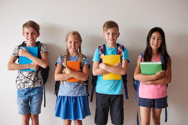 Cuatro niños sonrientes sosteniendo libros
