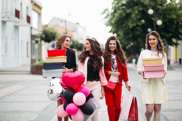 Cuatro novias de moda con cajas de zapatos en la calle.