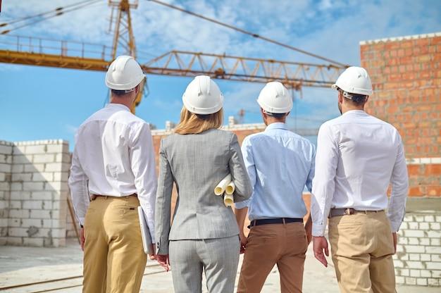 Cuatro personas examinando en cascos de seguridad un nuevo objeto de construcción