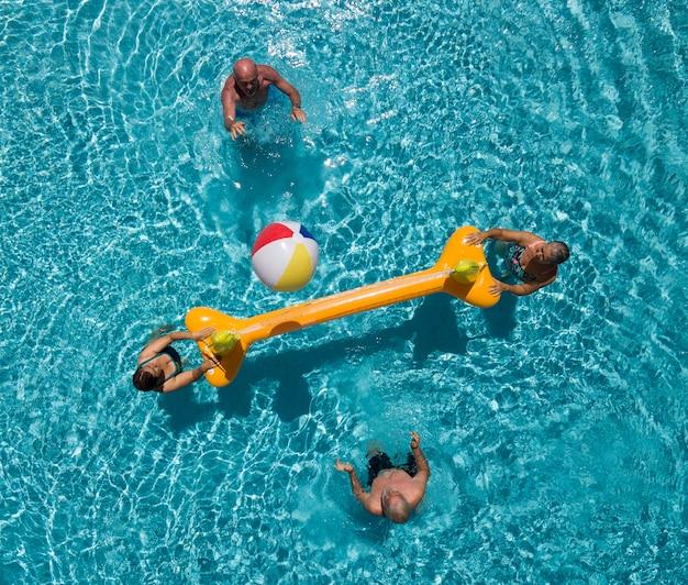 Cuatro personas mayores en la piscina con red inflable y pelota. dos hermanos mayores y sus esposas divirtiéndose. luz brillante del sol