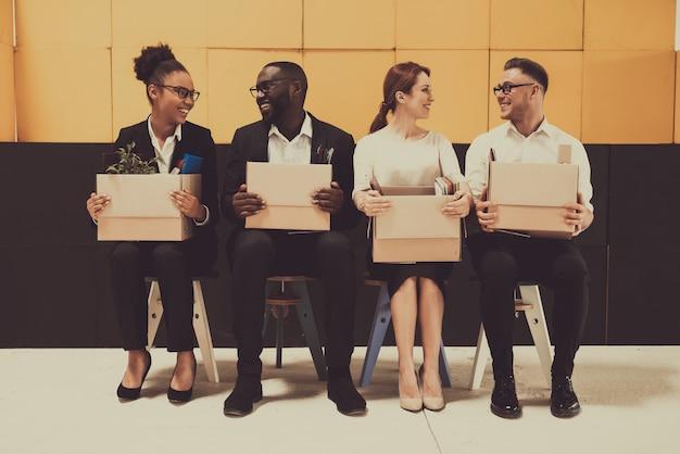 Cuatro personas sonrientes están sentadas con cajas de oficina.