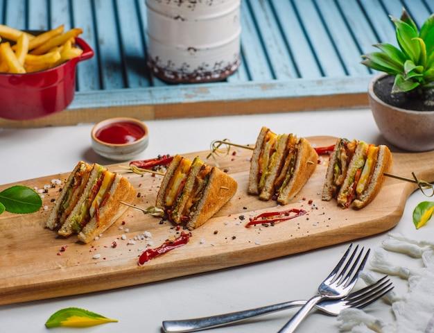 Cuatro piezas de sándwich club sobre tabla de madera con papas fritas, salsa de tomate