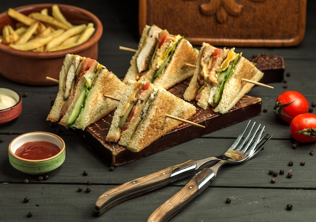 Cuatro porciones pequeñas de sándwich club de pollo en brochetas de bambú