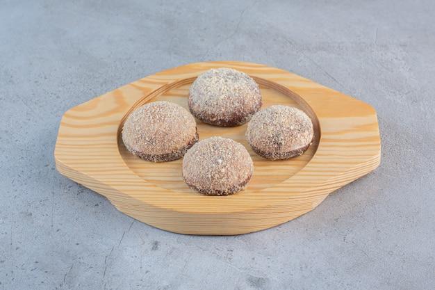 Cuatro sabrosas bolas de trufa colocadas en un plato de madera.