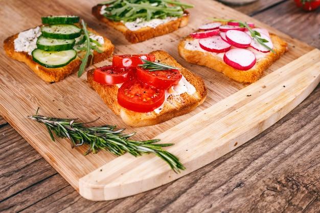 Cuatro sándwiches con verduras frescas, tomates, pepinos, rábanos y rúcula sobre un fondo de madera.