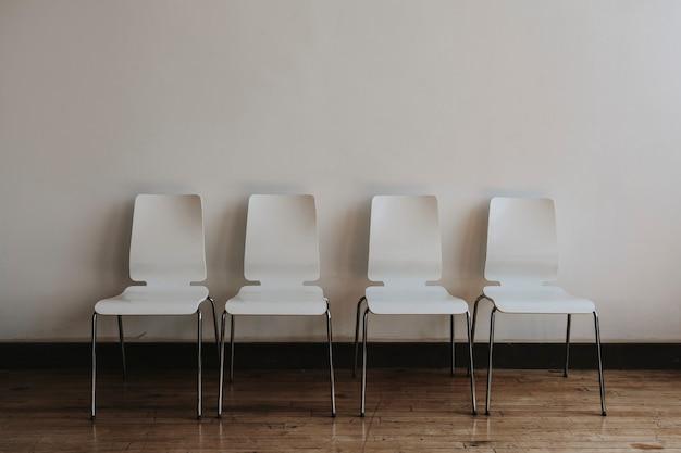 Cuatro sillas blancas vacías en una habitación.