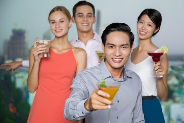 Cuatro sonriente los hombres y las mujeres con cócteles en la fiesta