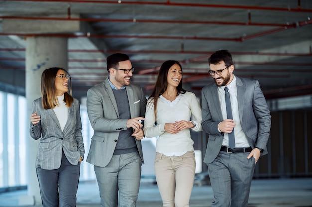 Cuatro sonrientes empresarios exitosos positivos visitando edificio en proceso de construcción.