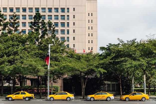Cuatro taxis amarillos que esperan a clientes a lo largo de la calle en taipei, taiwán.