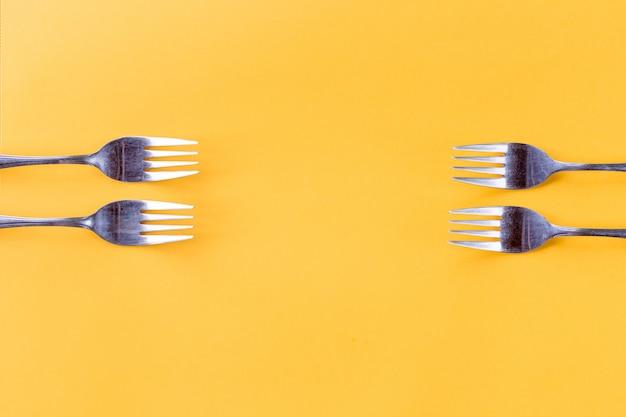 Cuatro tenedores sobre fondo amarillo