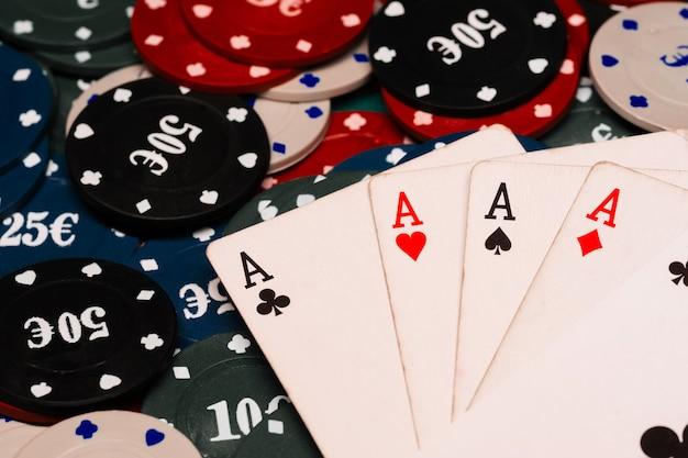Cuatro tipos de ases en el póker en el fondo de la mesa verde en el casino con fichas