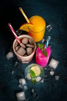Cuatro tipos de bebidas refrescantes con hielo sobre una superficie azul oscura y cubitos de hielo.