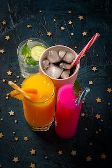 Cuatro tipos de bebidas refrescantes con hielo sobre una superficie azul oscuro y estrellas.