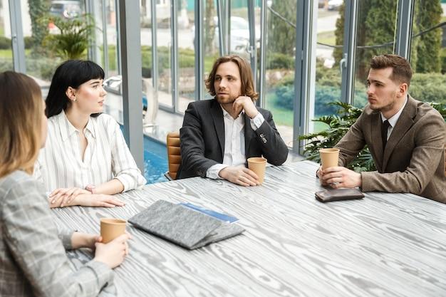 Cuatro trabajadores de oficina están sentados en una reunión