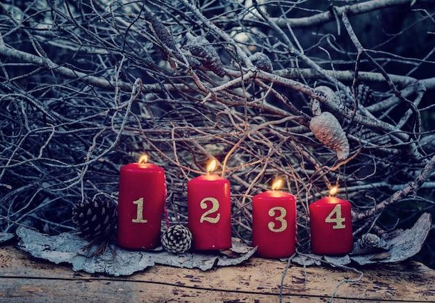 Cuatro velas rojas de adviento con números.