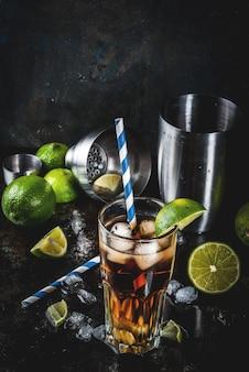 Cuba libre, long island o cóctel de té helado con alcohol fuerte, cola, lima y hielo, dos vasos, copyspace oscuro