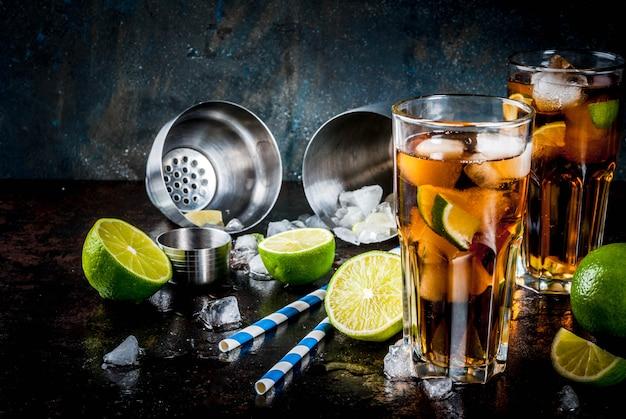 Cuba libre, long island o cóctel de té helado con alcohol fuerte, cola, lima y hielo, dos vasos, oscuro