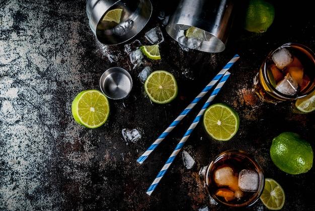 Cuba libre, long island o cóctel de té helado con alcohol fuerte, cola, lima y hielo, dos vasos, vista superior oscura