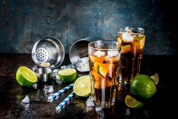 Cuba libre, long island o cóctel de té helado con alcohol fuerte, cola, lima y hielo, dos vasos