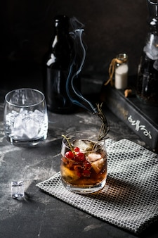 Cuba libre o cóctel de té helado long island con bebidas fuertes, refrescos de cola, lima y hielo en vaso, bebidas frías o limonada. cóctel con fuego. cóctel con humo.