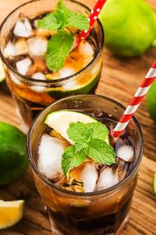 Cuba libre recién hecha con ron marrón, cola, menta y limón en la mesa de madera