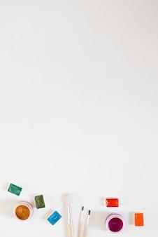 Cubetas con pinturas de acuarela multicolores y pinceles, frascos con gouache sobre un fondo blanco. borde con herramientas de dibujo. copiar espacio para texto