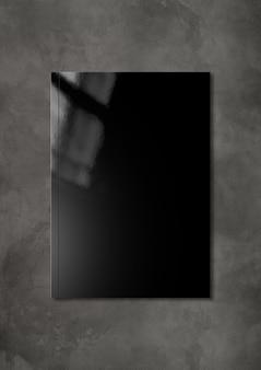 Cubierta de folleto negro aislado sobre fondo de hormigón oscuro
