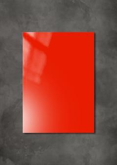 Cubierta de folleto rojo aislada sobre fondo de hormigón oscuro, plantilla de maqueta
