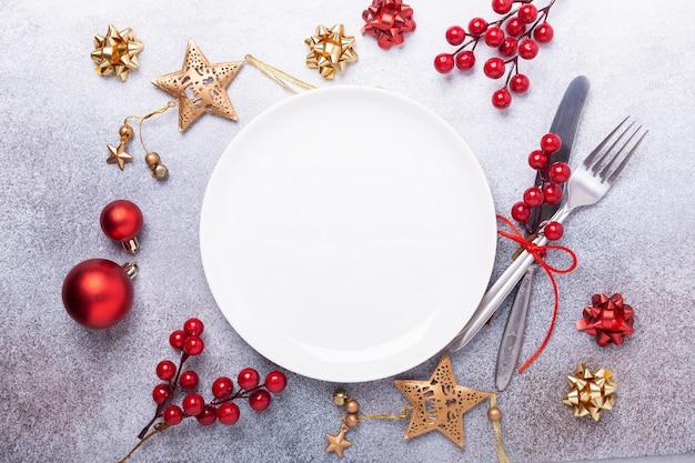 Cubierto de mesa de navidad con plato blanco vacío, cubiertos con decoraciones festivas sobre fondo de piedra
